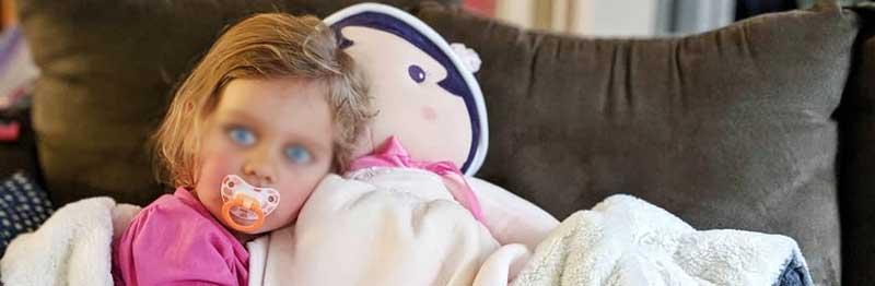 grande poupee dans les bras d'un enfant