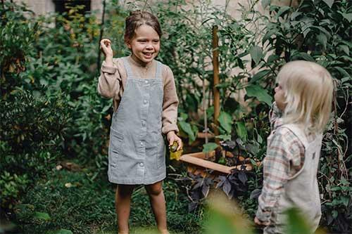 deux enfants qui parlent dans un jardin