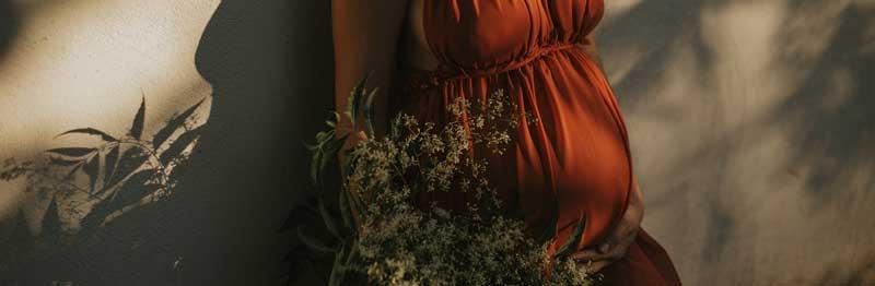 femme qui attend un bébé en robe rouge