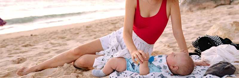 maman qui couche son bébé sur la plage