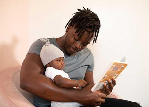 papa lit un livre à bébé