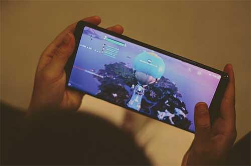enfant qui joue à fortnite sur une tablette